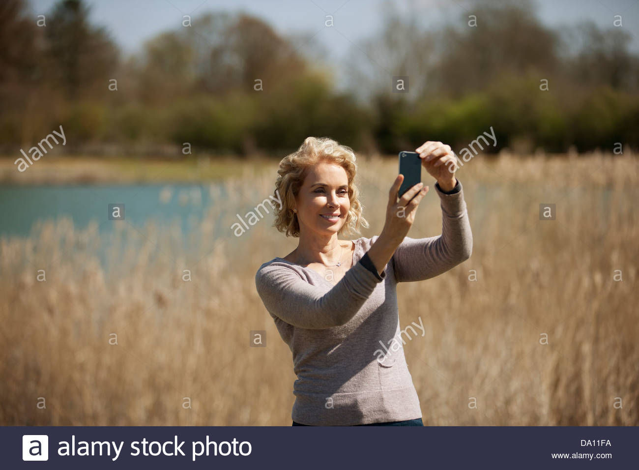 A mature woman in the countryside, taking a photo with a smartphone - Stock Image