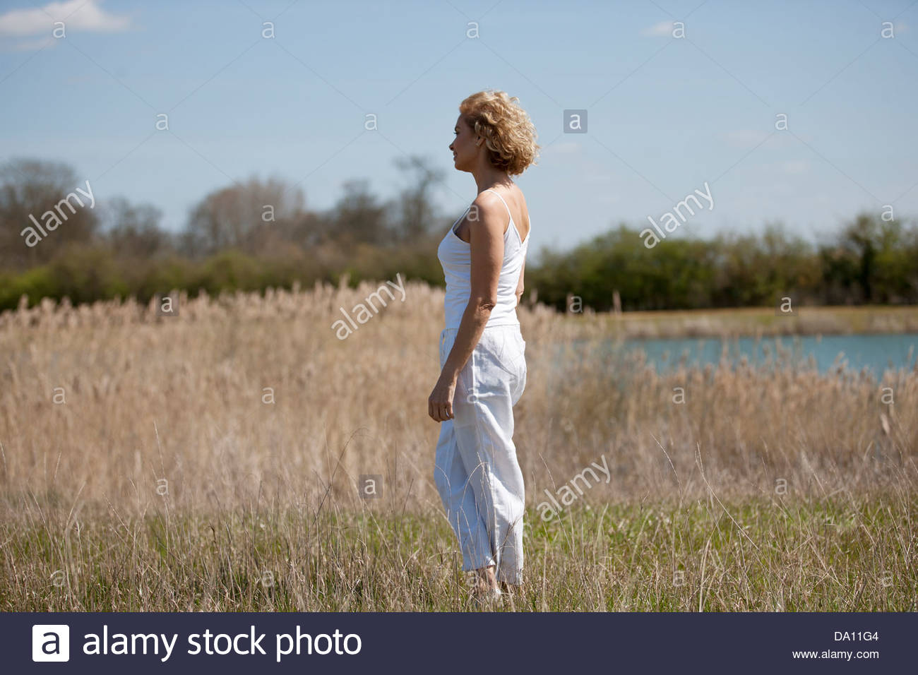A mid adult woman standing in the countryside in summertime - Stock Image