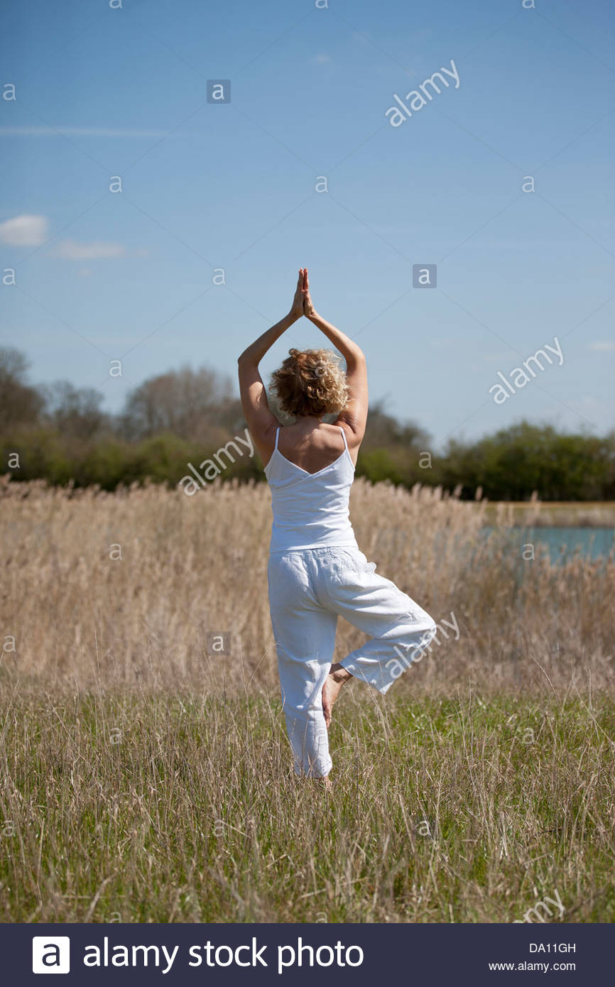 A mid adult woman practising yoga in the countryside in summertime - Stock Image