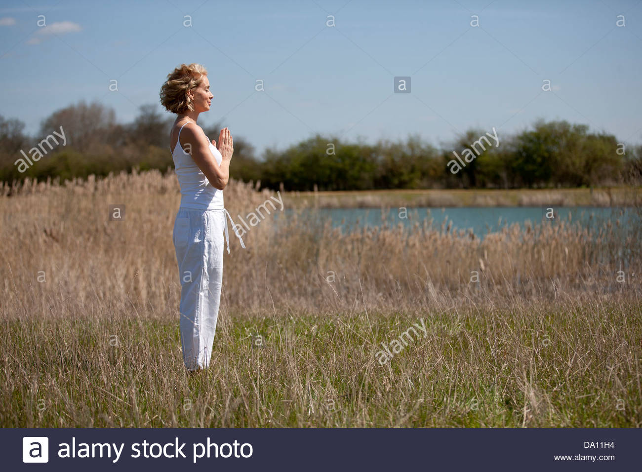 A mid adult woman practicing yoga in the countryside in summertime - Stock Image