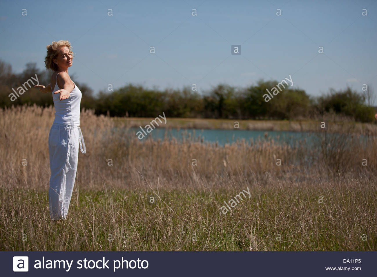A mature woman practicing yoga in the countryside in summertime - Stock Image