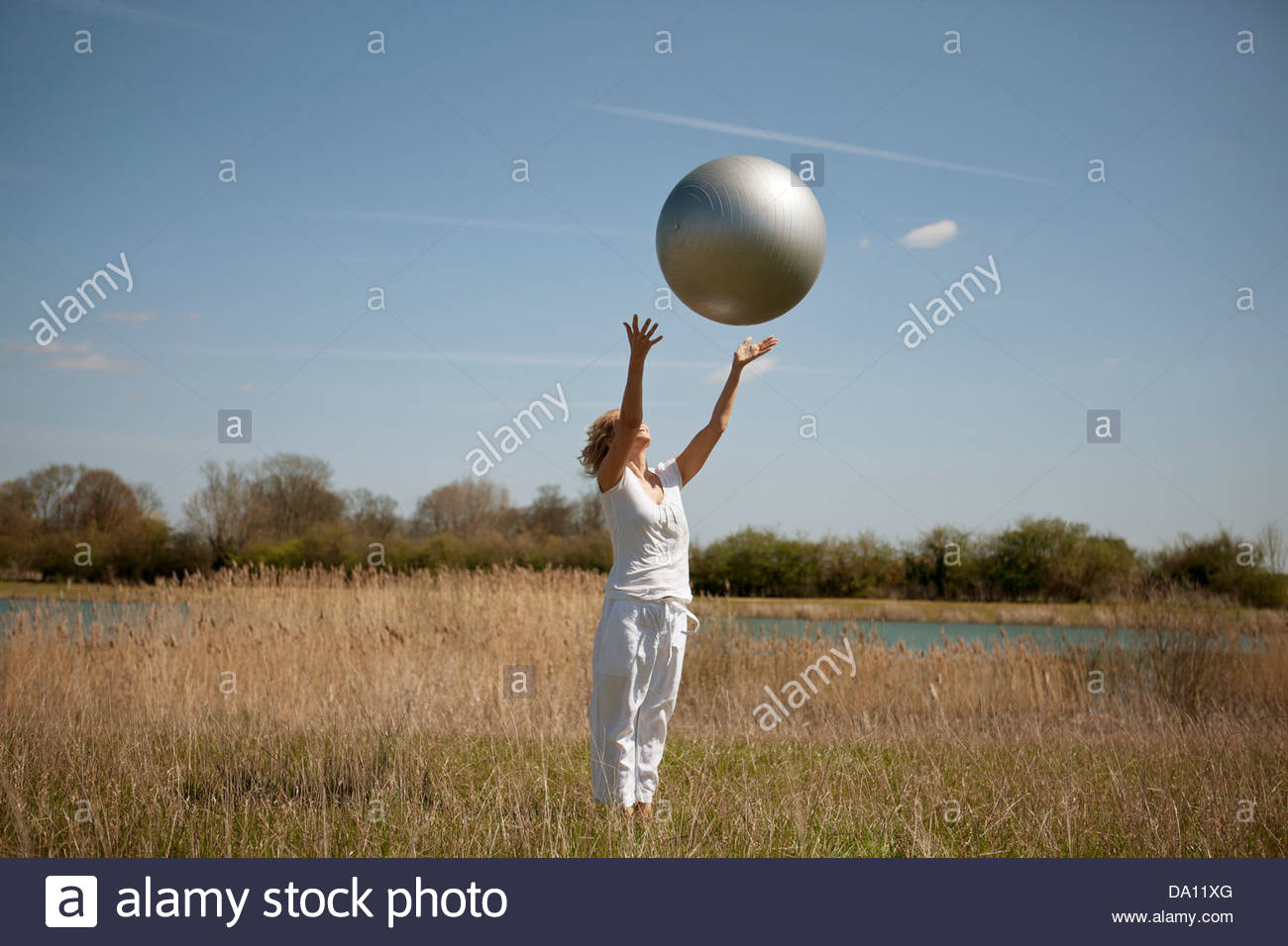 A mature woman catching an exercise ball - Stock Image
