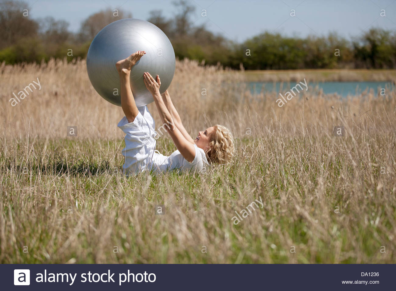 A mature woman exercising with an exercise ball - Stock Image