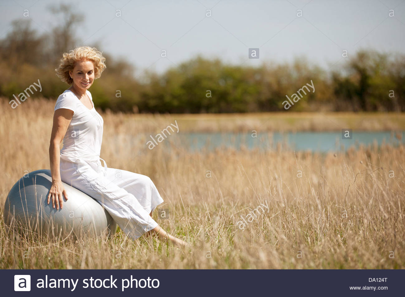 A mature woman sitting on an exercise ball - Stock Image
