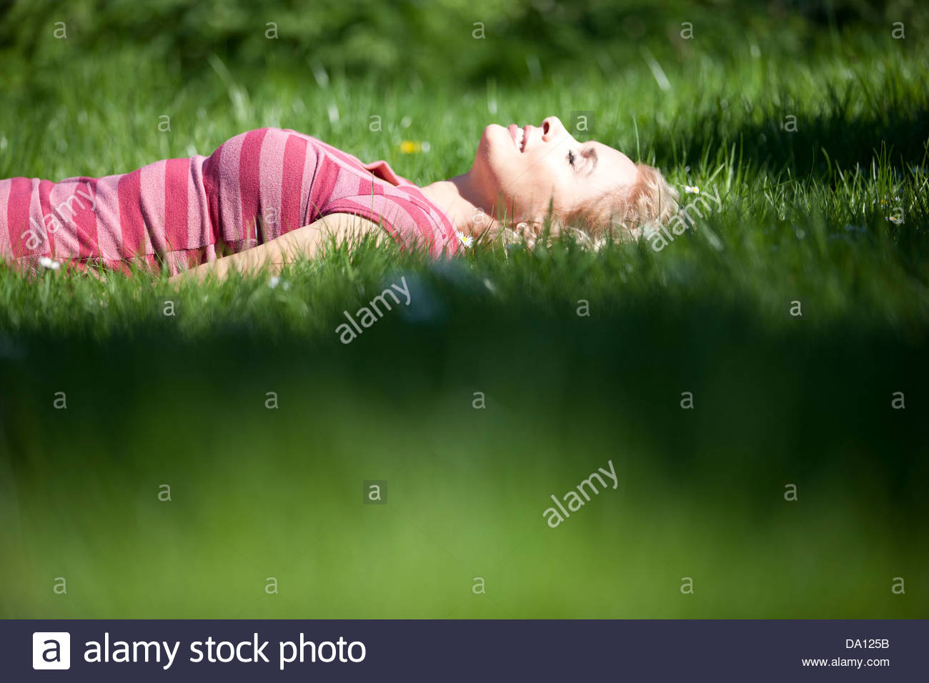 A mature woman laying in the grass in summertime, smiling - Stock Image