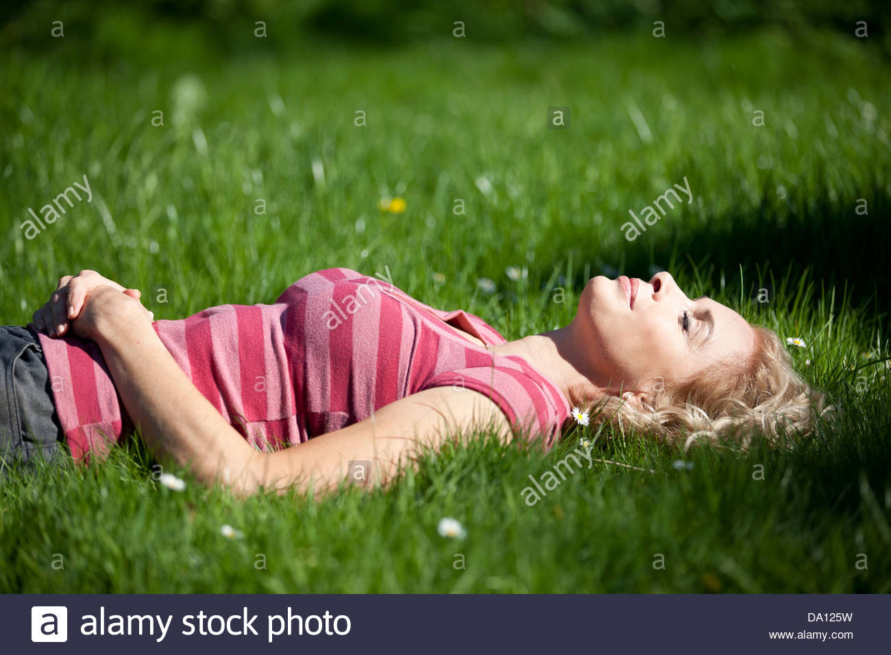 A mature woman laying in the grass in summertime - Stock Image