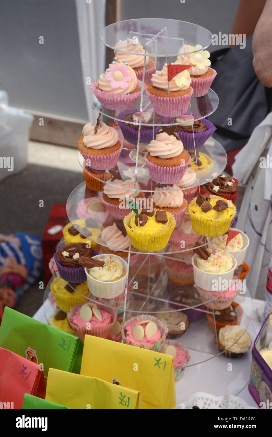 Home made cakes on sale by volunteer mums on a stall at a primary school summer fair - Stock Image