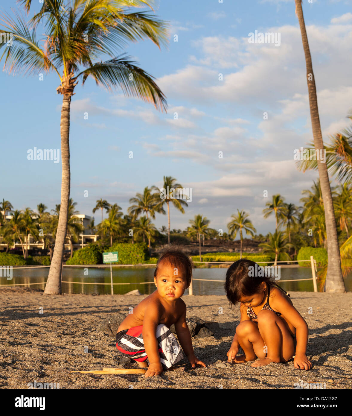Brother and sister at Anaehoomalu Beach on the Big Island of Hawaii, with the historic fish pond and Marriott in - Stock Image
