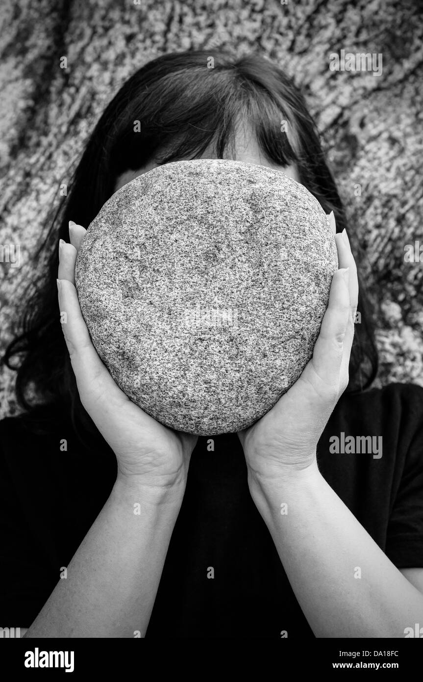Woman holding a big stone - Stock Image