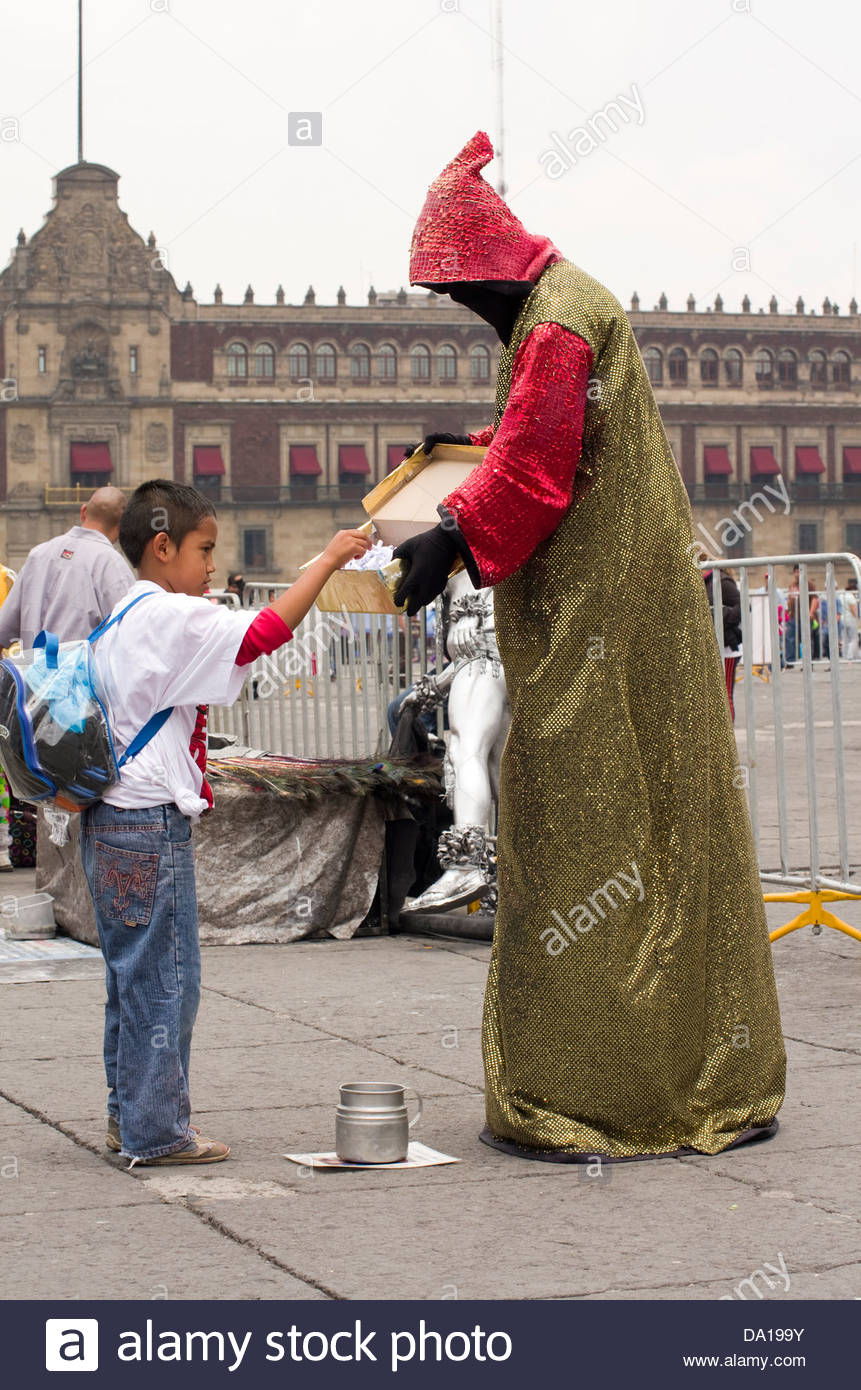 A fortune teller allows a child to select his fortune during a street performance at the Zocalo in Mexico City. - Stock Image
