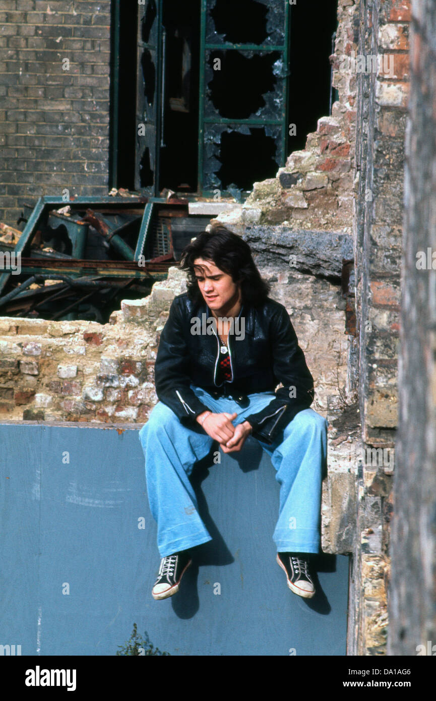 Young man 1970s teenager sitting at the Odhams derelict construction site in the Covent Garden area of London UK - Stock Image
