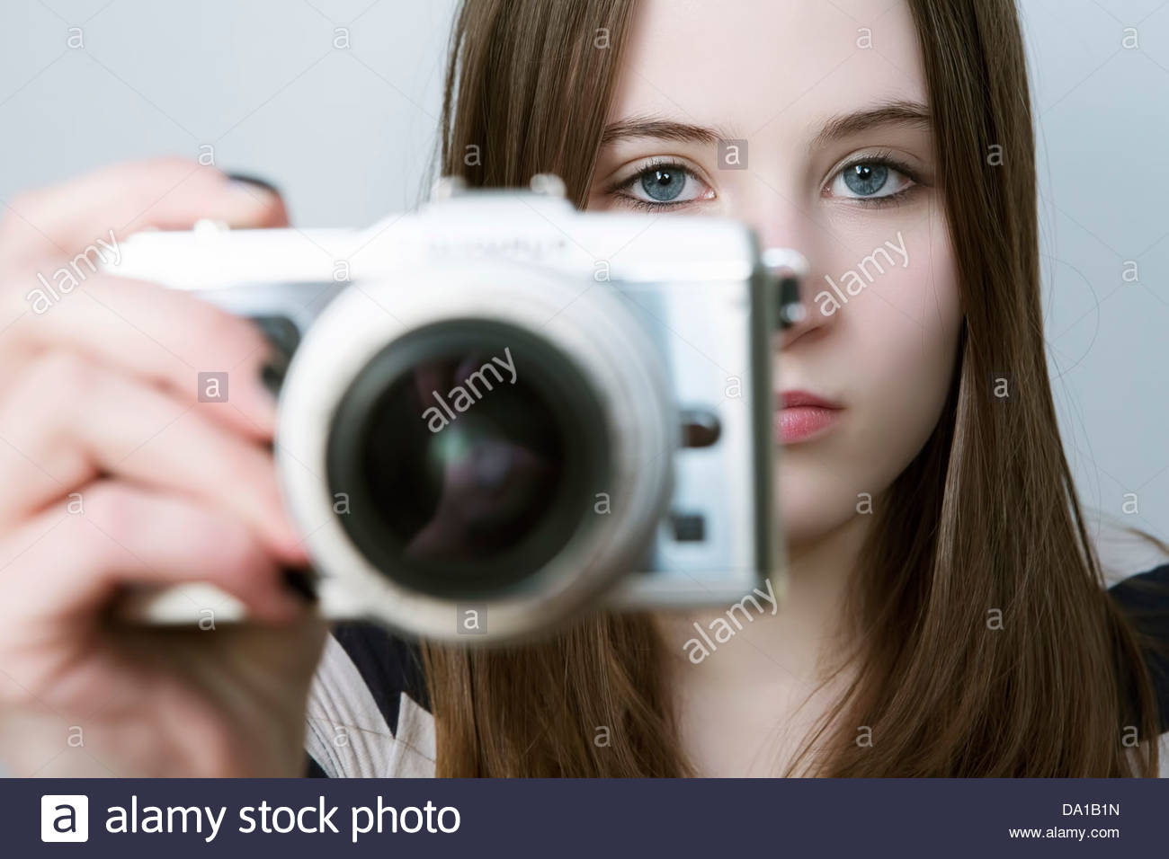 Portrait of Teenage girl holding digital camera - Stock Image