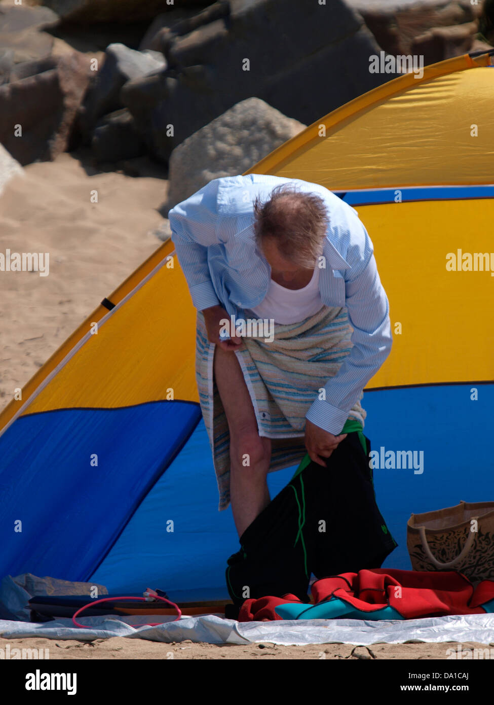 Old man trying to put on swim shorts on with towel around waist at the beach, Cornwall, UK 2013 - Stock Image