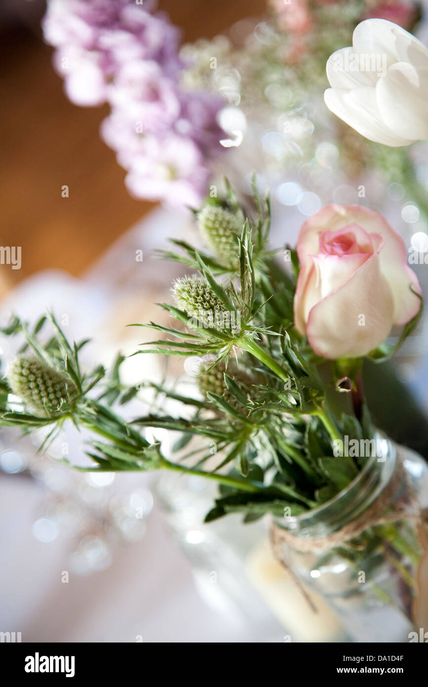 Simple Flower Arrangement In A Jar Decorating Tables At Wedding Reception  Venue With Tea Rose And Thistle
