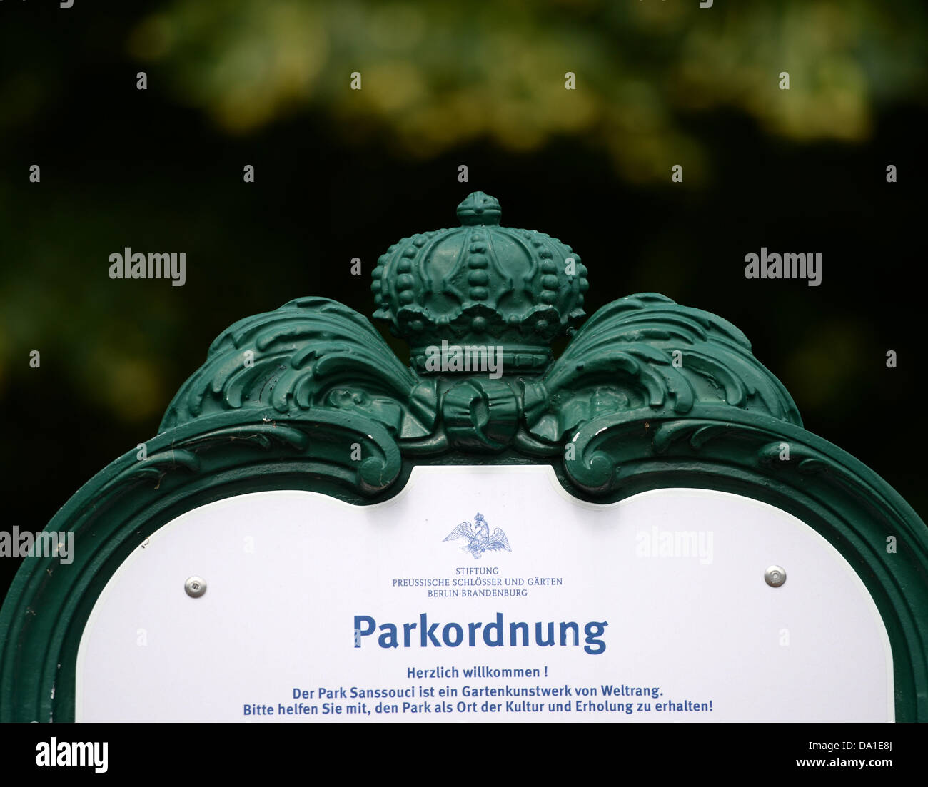 A sign reads 'Parkordnung' ('Park rules') at the entrance of world heritage park Sanssouci in Potsdam, - Stock Image