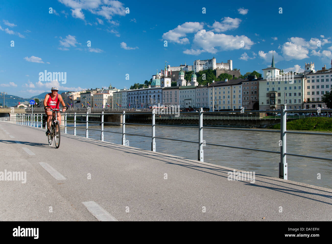 Cyclist riding in  the bike lane along Salzach River, Salzburg, Austria - Stock Image