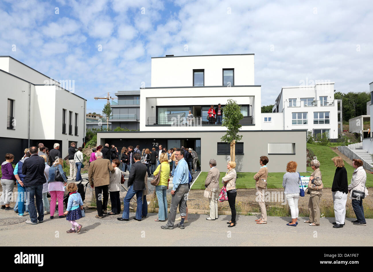 Visitors queue around to visit a newly build single-family house in the Lake Phoenix Estate of Dortmund, Germany - Stock Image