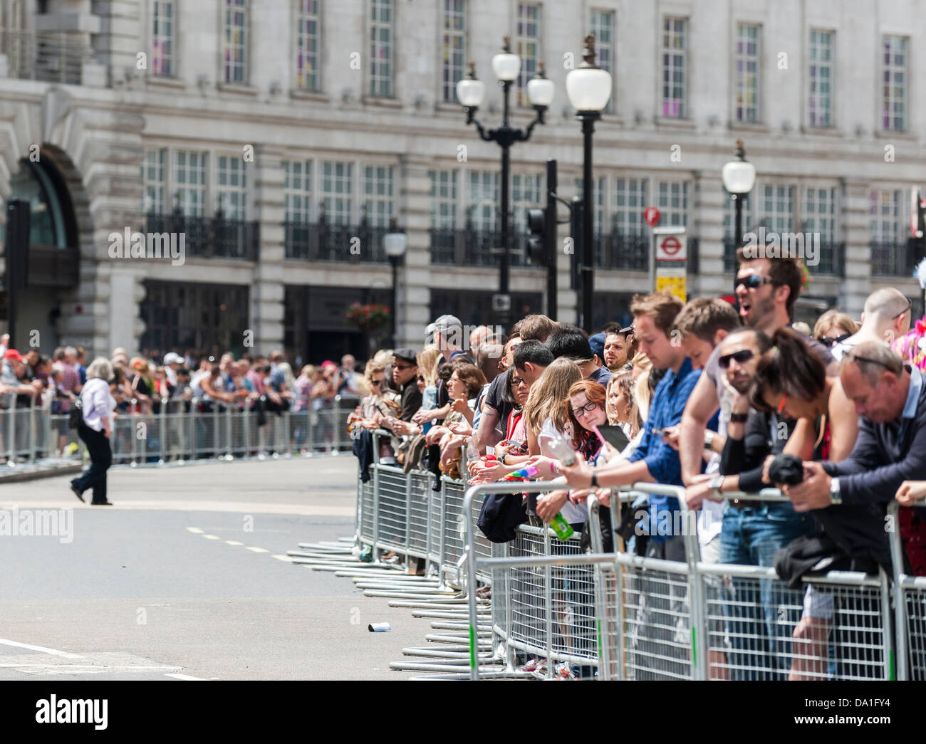 Crowds gathering to watch the London Pride parade. - Stock Image