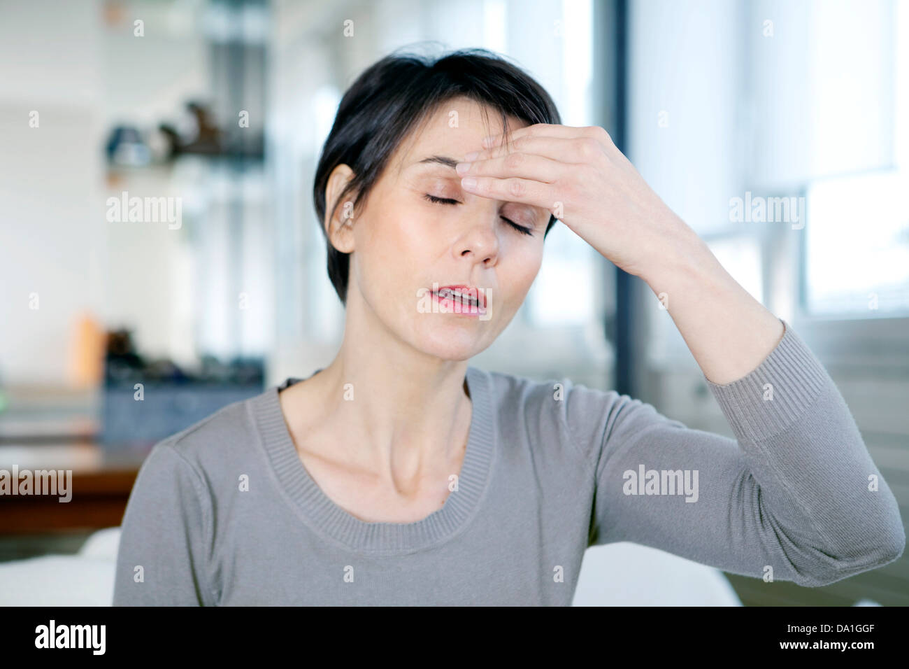 WOMAN WITH A MIGRAINE - Stock Image