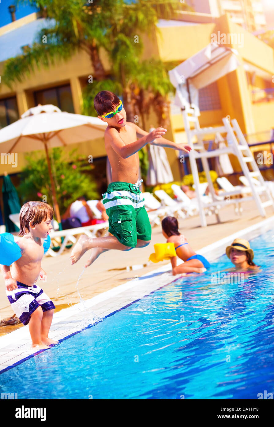 Happy family having fun in the pool, son jumping into the water, relaxed in aquapark, beach resort, summer vacation - Stock Image