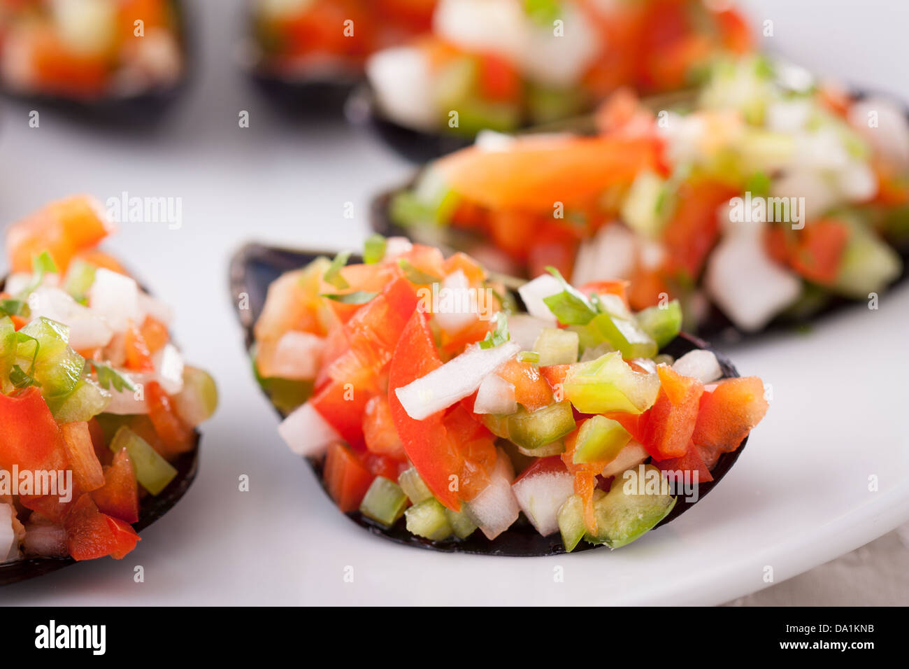 Steamed mussels with vegetable mince on a white dish Stock Photo
