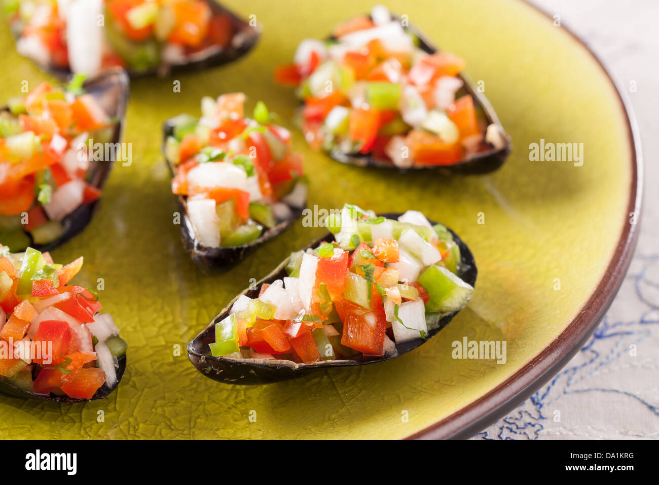 Steamed mussels with vegetable mince on a green dish Stock Photo
