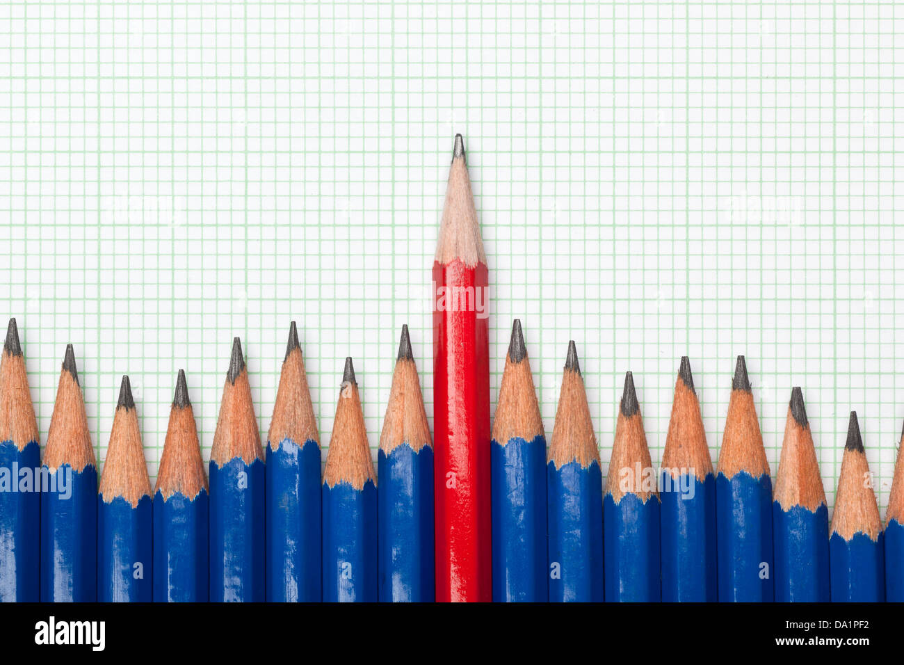 Red pencil standing out from a row of blue pencils on a piece of graph paper - Stock Image