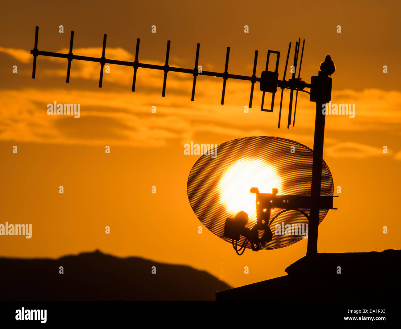 Sunset over a TV aerial in the Lake District, UK, with a Robin using it as a song post. - Stock Image