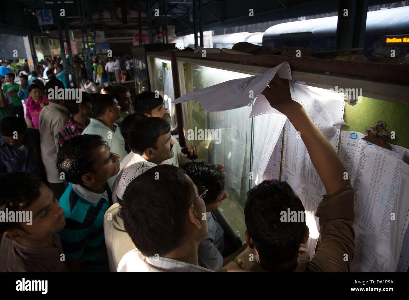Passengers checking seating and standby lists at Chattrapati Shivaji or Victoria Terminus, Mumbai, India - Stock Image