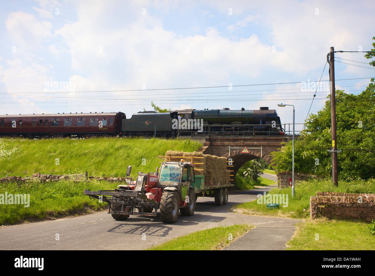 LMS Royal Scot Class 6115 Scots Guardsman steam train at Plumpton on the West Coast Main Line Railway with telehandler. - Stock Image