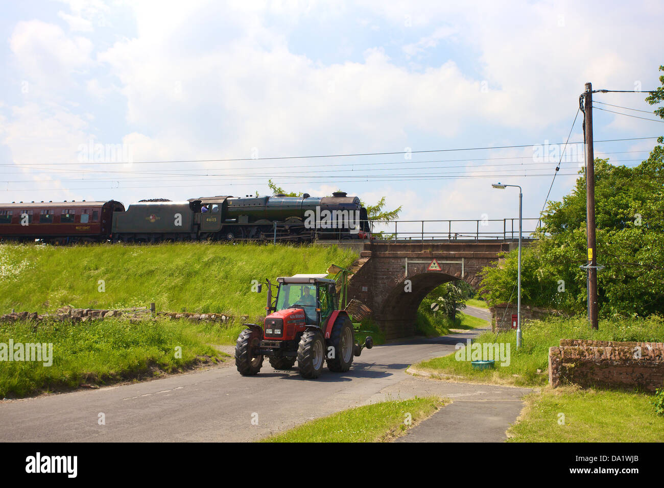 LMS Royal Scot Class 6115 Scots Guardsman steam train at Plumpton on the West Coast Main Line Railway with tractor. - Stock Image