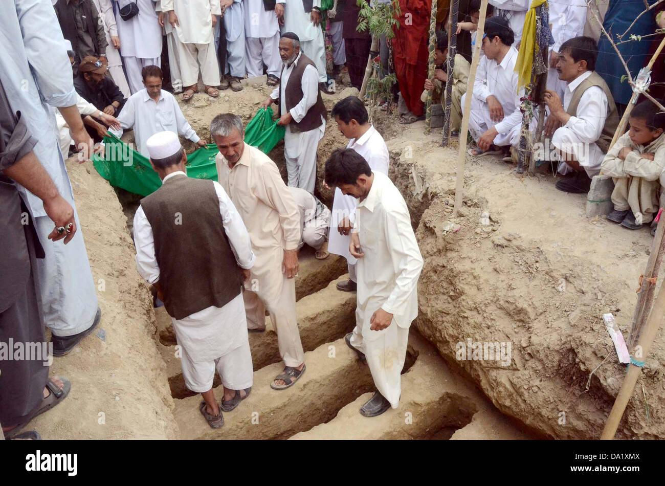 Shiite mourners Bury dead bodies of suicide bomb blast victims of Aliabad area of Hazara town after their funeral - Stock Image