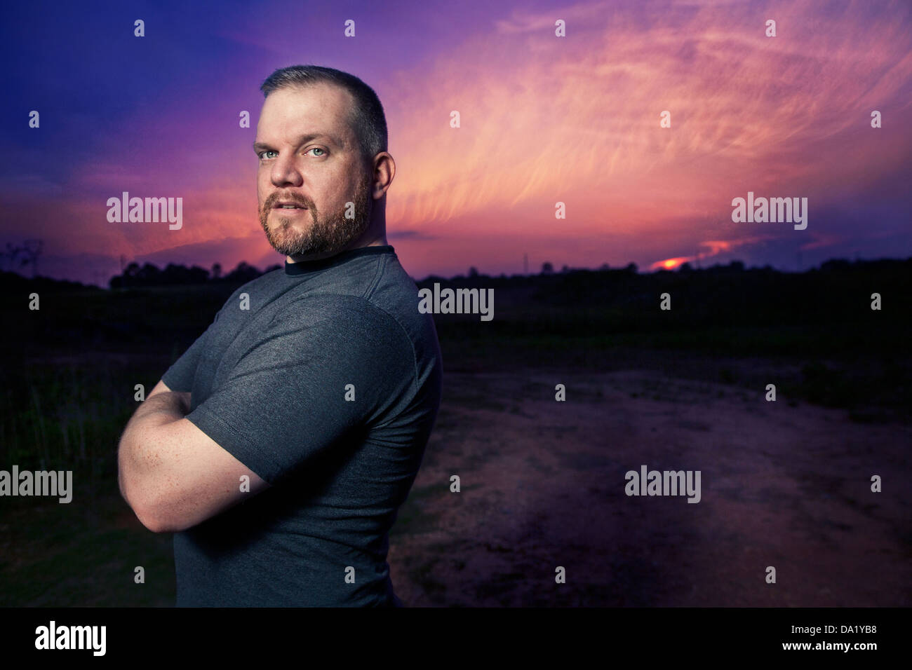 Man stands against dusk sky - Stock Image