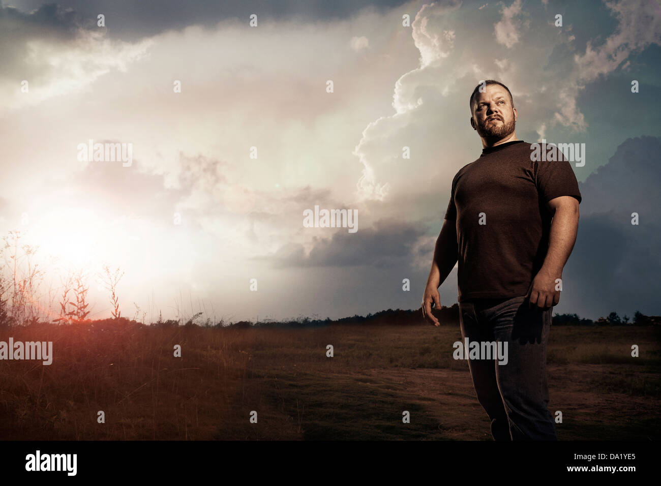 Man standing in front of sunset in open field - Stock Image
