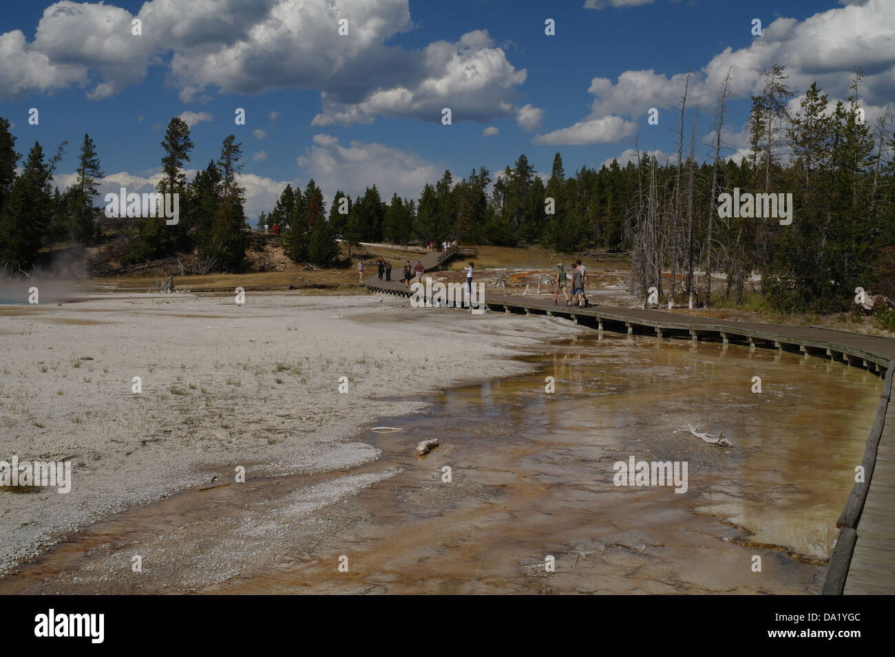 Blue sky white clouds view boardwalk tourists crossing orange bacterial overflow Silex Spring, Lower Geyser Basin, - Stock Image
