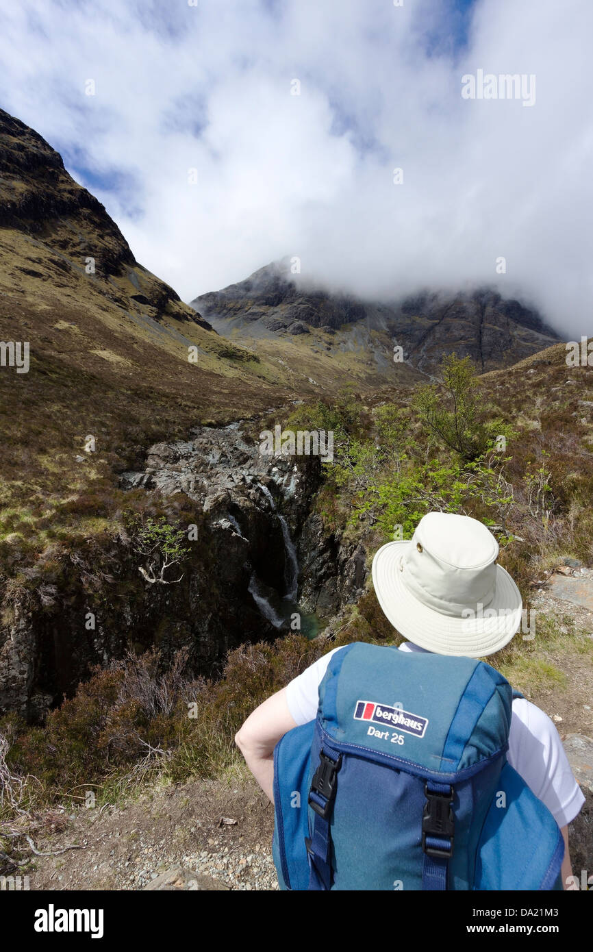 Hillwalker with sun hat and backpack on mountain path to Blaven, Isle of Skye, Scotland, UK - Stock Image