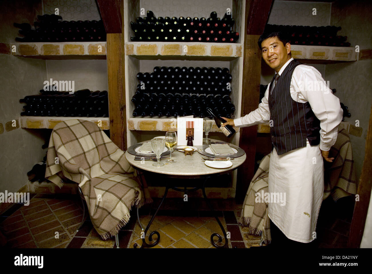 There are a number of unique dining venues, including this one in the wine cellar, at Huka Lodge, Taupo, New Zealand. - Stock Image