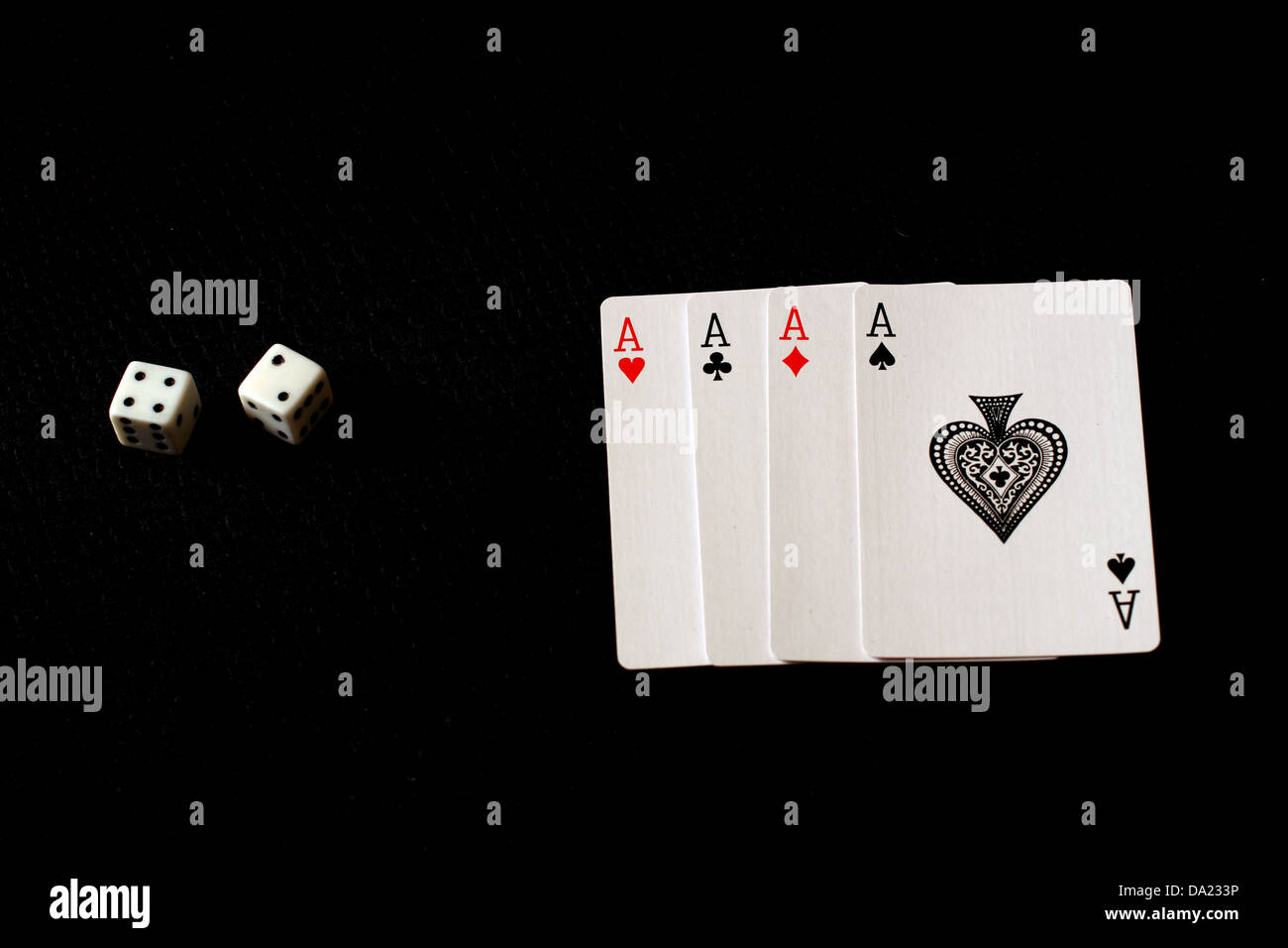 4  playing cards showing,club,diamond, and to dices showing numbers 2 and 4 on a black backdrop. - Stock Image