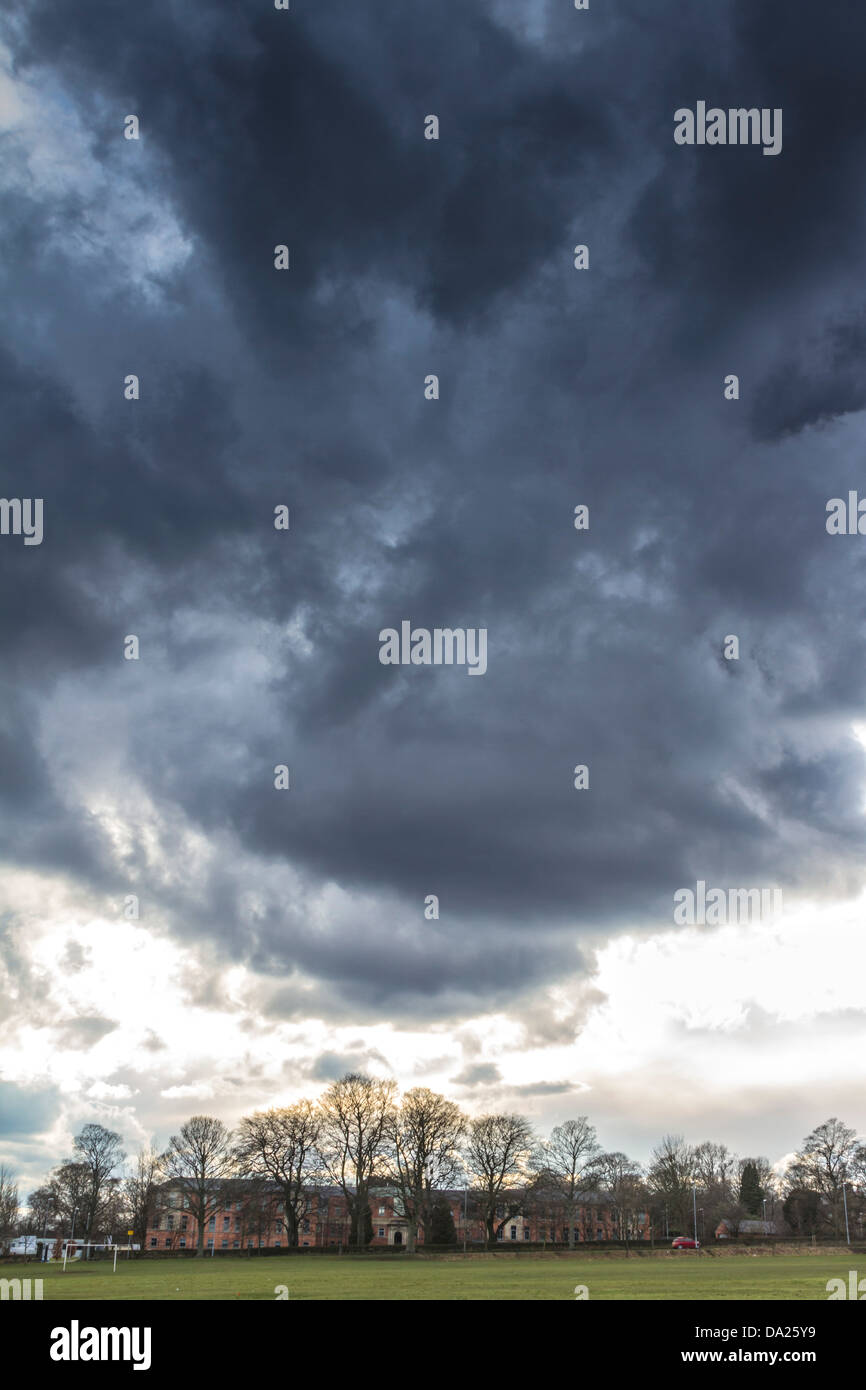 Dramatic image of heavy clouds over distant Roundhay School building in bottom third of image with plenty of room - Stock Image