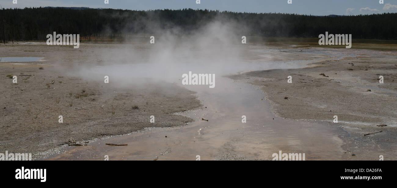 Blue sky view steam waters Celestine Pool, broad sinter plain, overflow bacterial mat stream, Lower Geyser Basin, - Stock Image