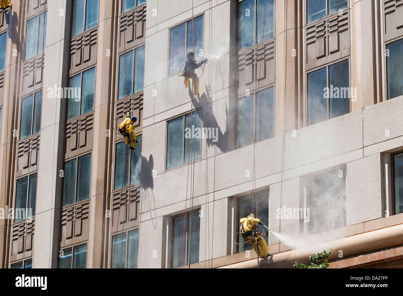 High rise building maintenance crew cleaning with pressure washer - Stock Image