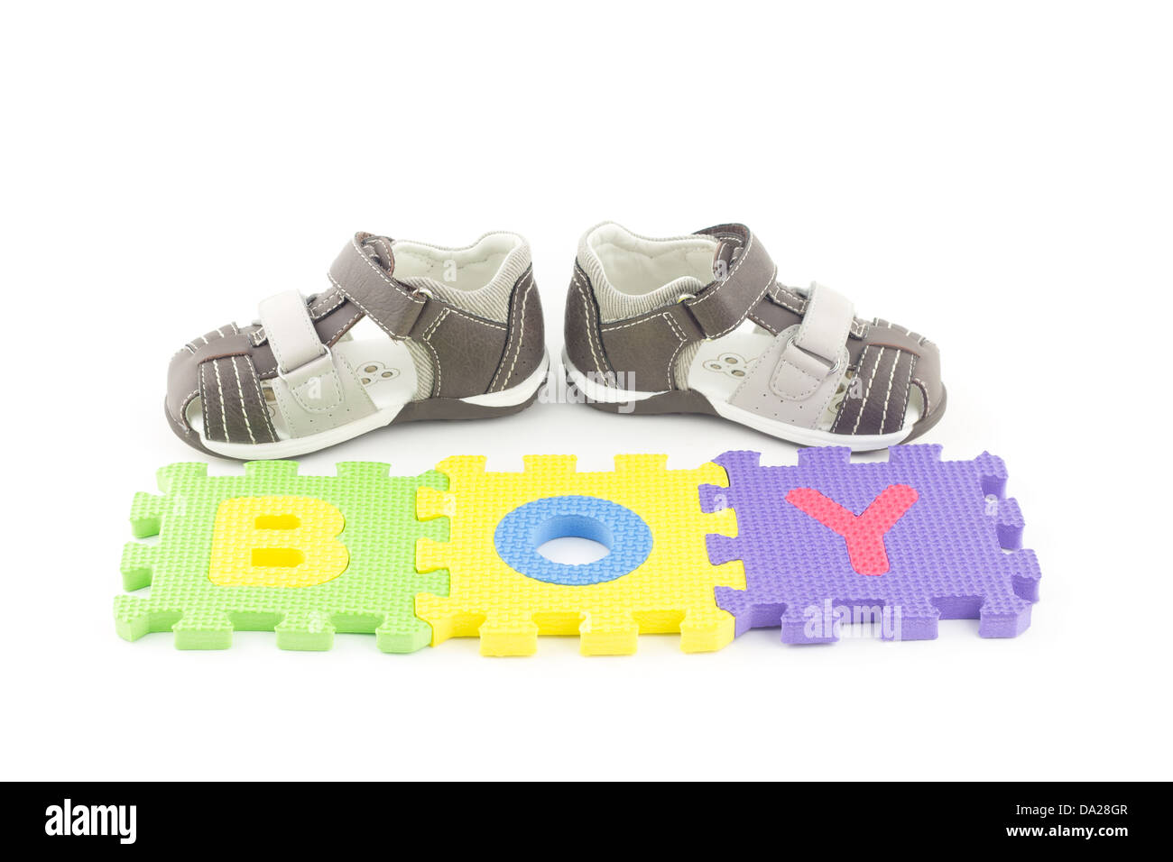Sandals of a toddler in front of alphabet puzzle pieces isolated on white background - Stock Image