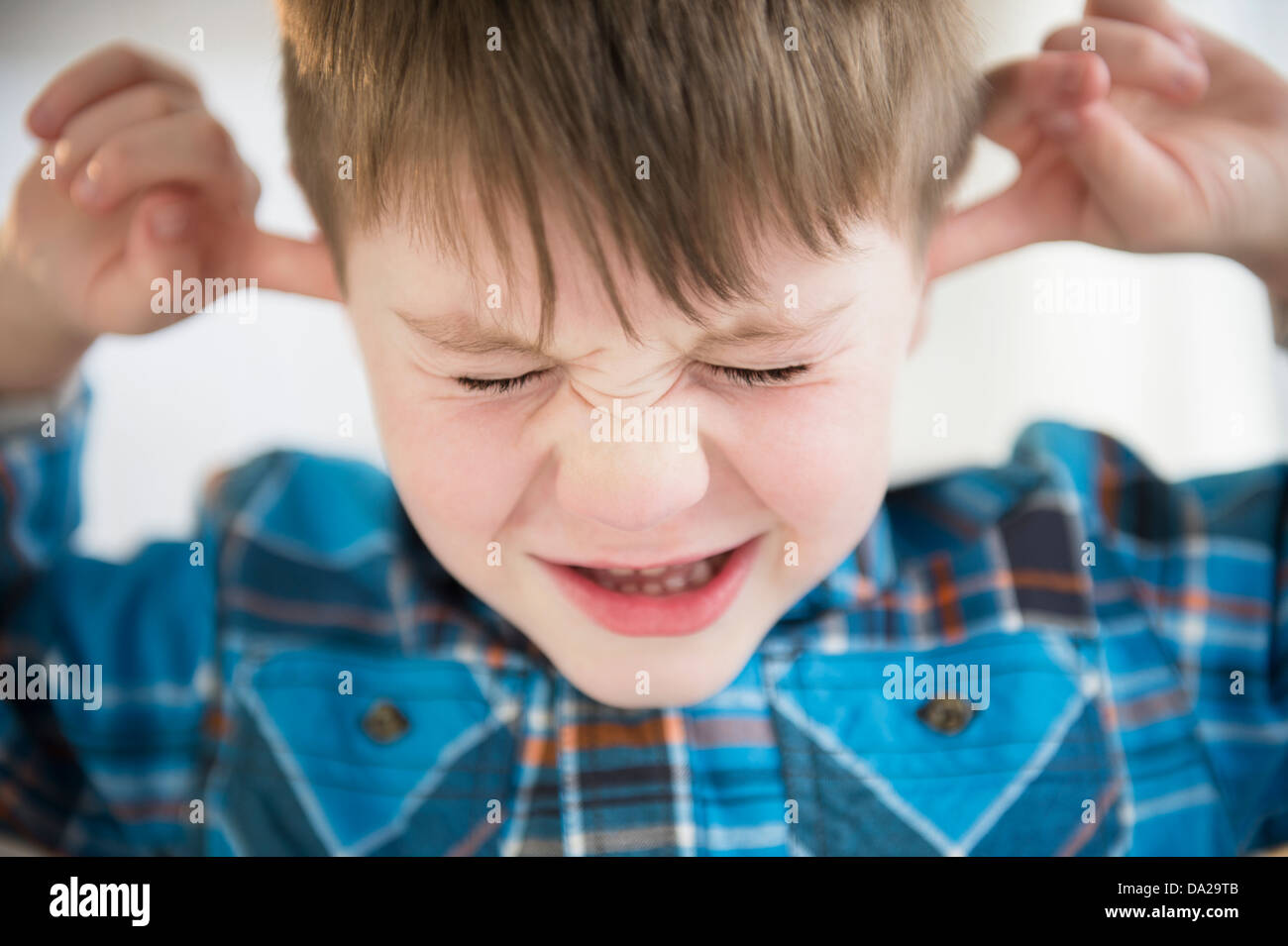 Portrait of boy (4-5) sticking fingers in his ears - Stock Image