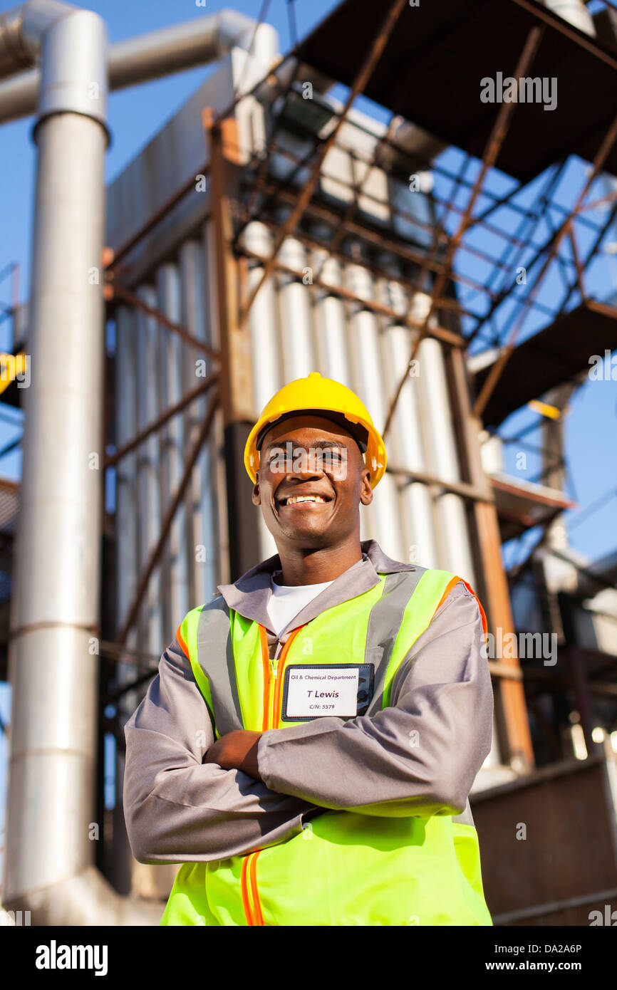 cheerful afro american oil industrial worker with arms crossed in refinery plant - Stock Image