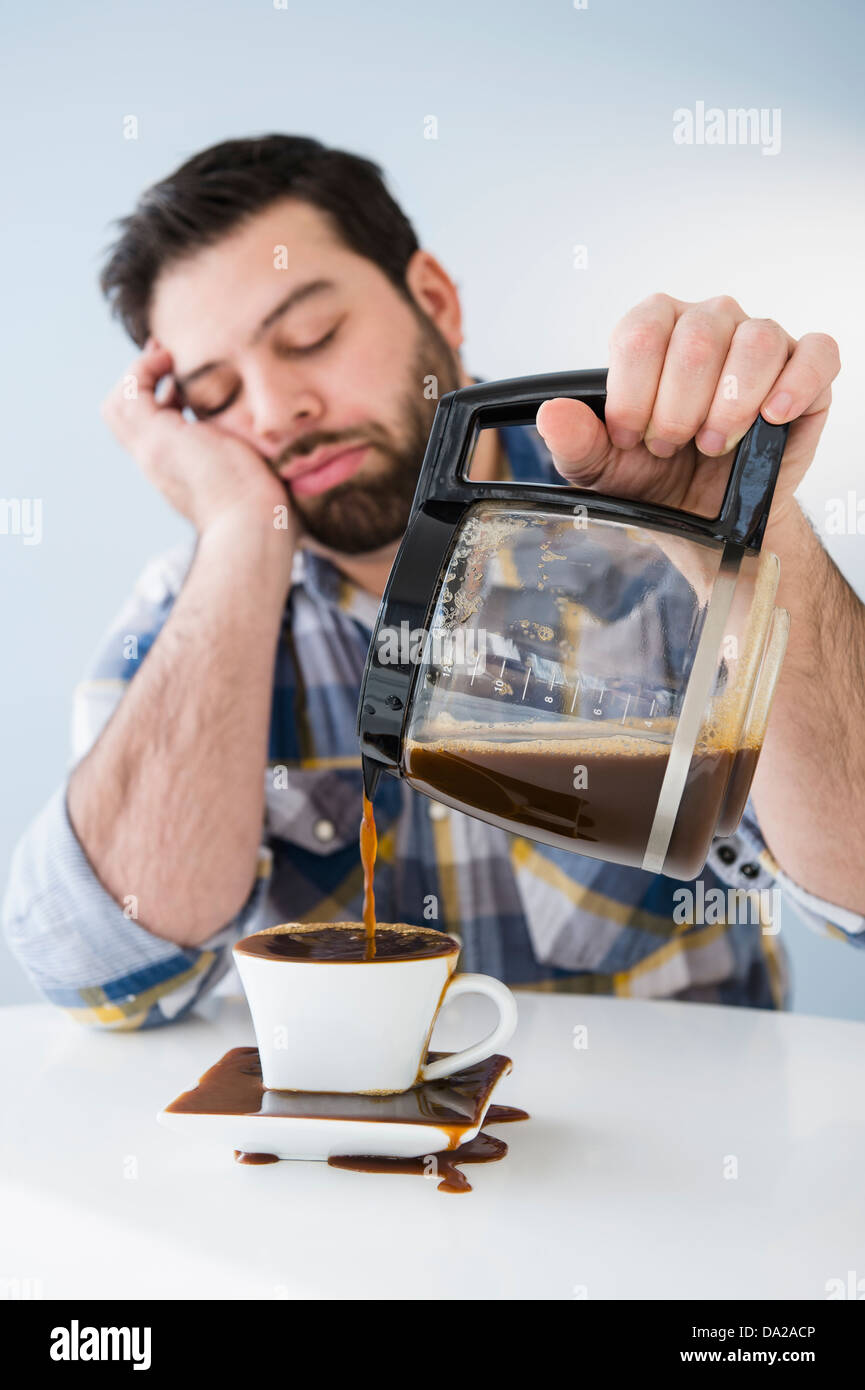 Tired, sleepy man spilling coffee on table - Stock Image