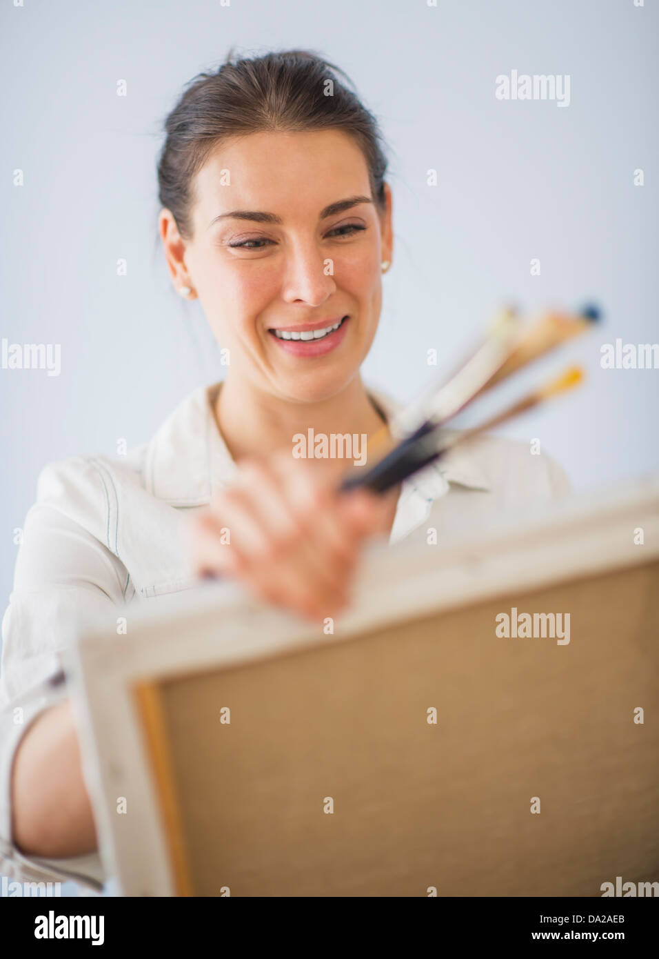 Studio Shot of woman holding paintbrushes and artist's canvas - Stock Image