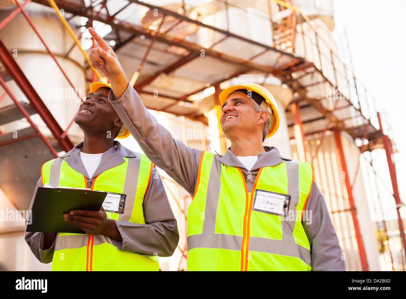 cheerful petrochemical co-workers working in the plant - Stock Image