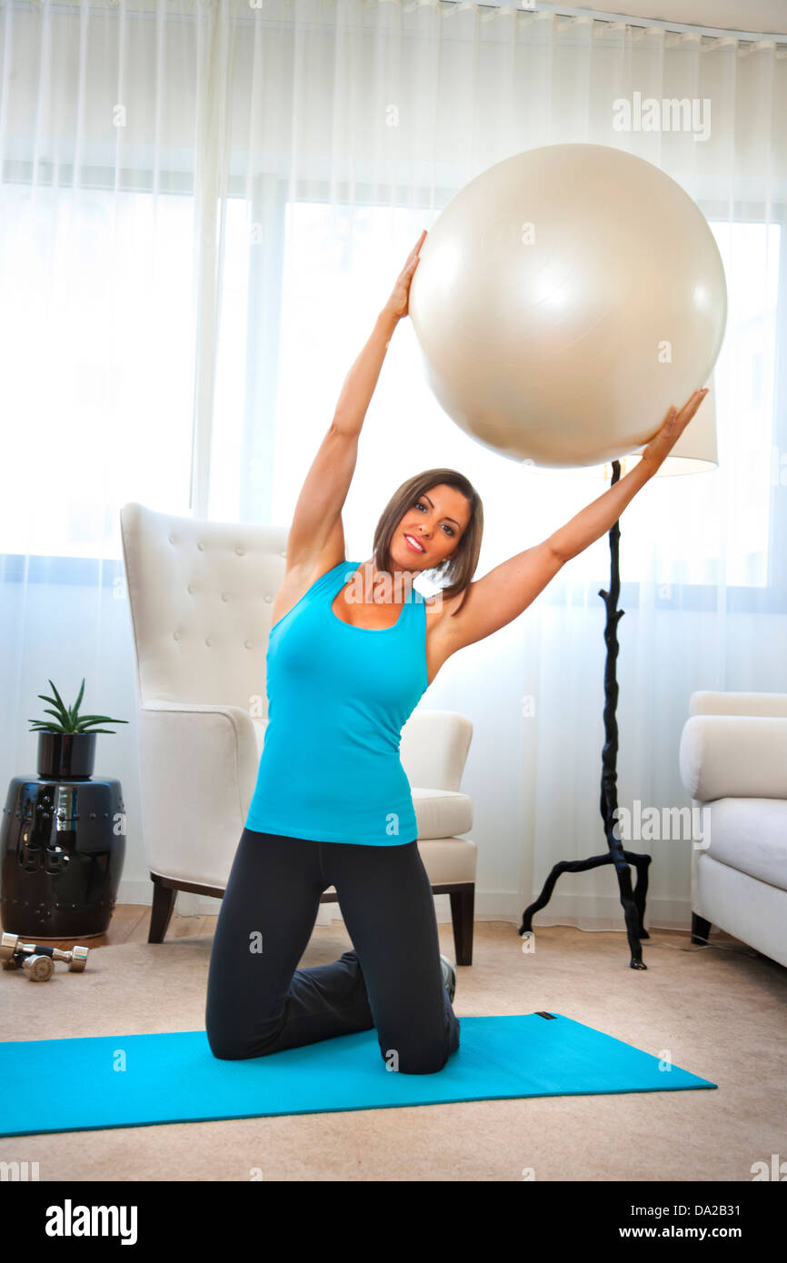 fitness trainer demonstrates exercises at home with fitness ball - Stock Image