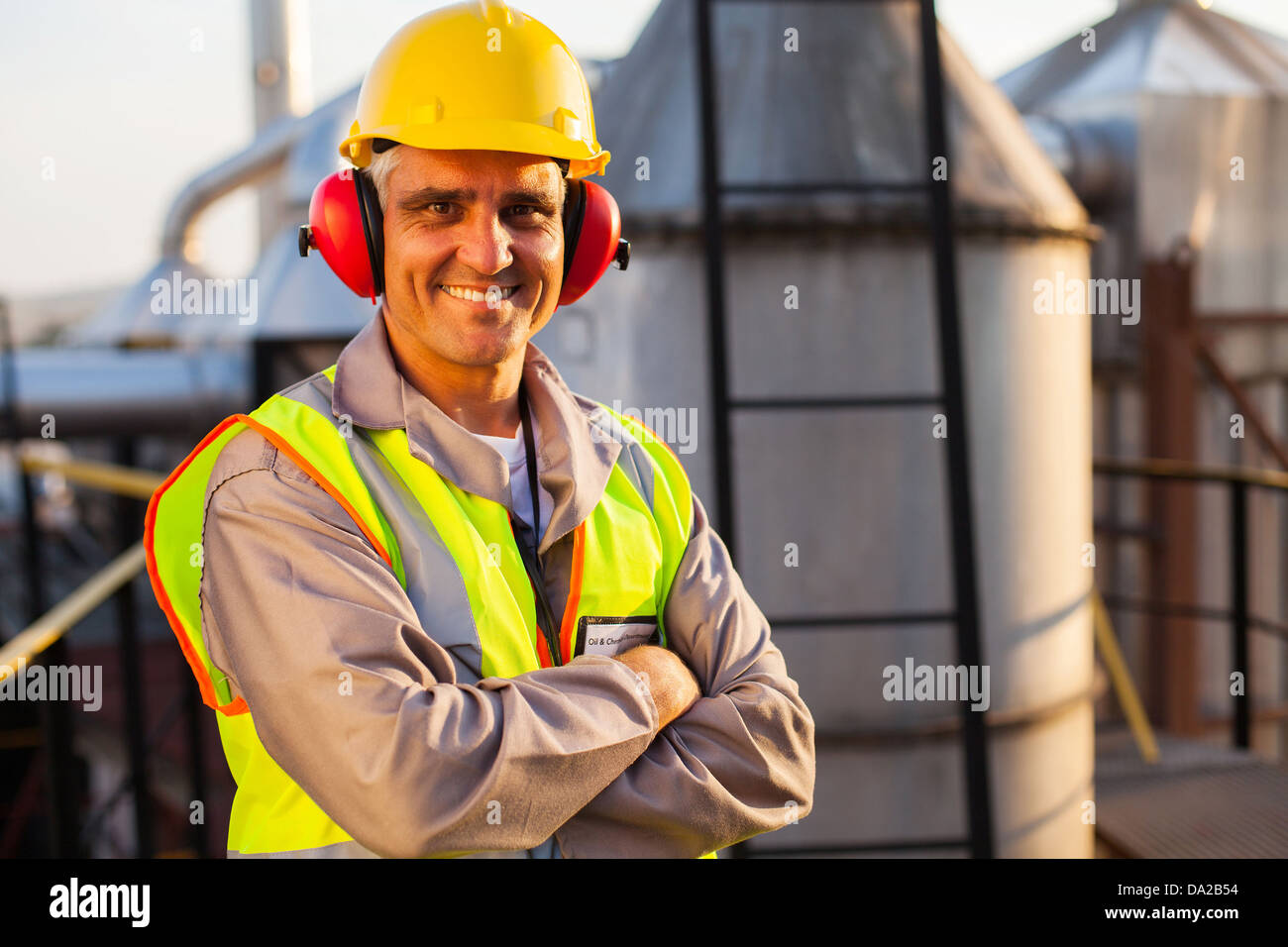 happy middle aged oil chemical industry worker inside plant Stock Photo