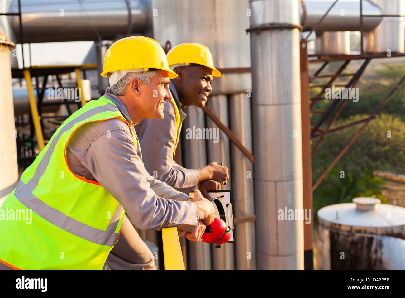 smiling industrial workers in safety gear - Stock Image